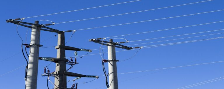 shot electric posts lines against blue background 2000x800 1